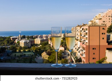 Two glasses of white wine in front of blue sea in Genoa