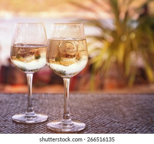 two glasses of white wine with ice on a table at the beach cafe. Image with retro toning