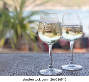 two glasses of white wine with ice on a table at the beach cafe