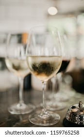 Two glasses of white wine on a bar. Hospitality and drinks concept. Selective focus on a glass of wine in the front. Refreshing, chilled drink.