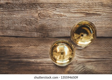 Two glasses of white wine on the wooden background
