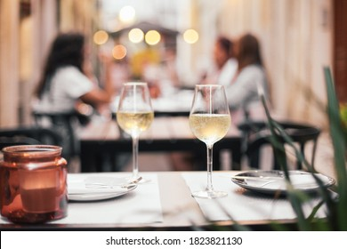 Two glasses of white wine on a table with candles, all set for a romantic dinner date, outdoor cafe