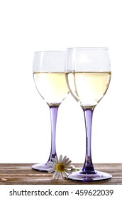Two glasses of white wine on a wooden table with a chamomile on