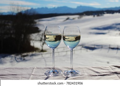 Two glasses of white wine on the balcony, dreamlike winter landscape with mountains in the background, happy moment