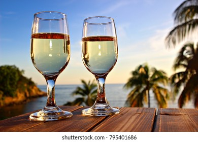 Two glasses of white wine on the sea and sky background, shallow focus