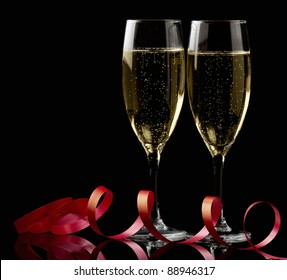 Two glasses with white wine over black background with red ribbon