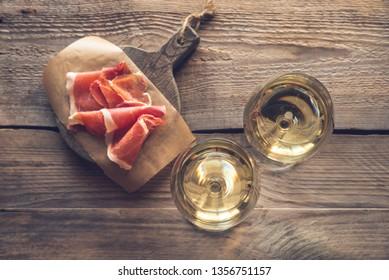 Two glasses of white wine with Prosciutto ham