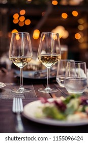 Two glasses with white wine in a restaurant. Romantic dinner with bokeh lights in back