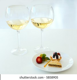 two glasses of white wine with sweets shallow dof