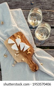 Two glasses of white wine and a wooden plate with cheese and nuts served outside at sunset.