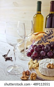 Two glasses of wine, Camembert cheese, nuts and a bottle of wine