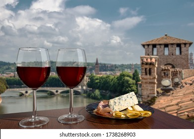 Two glasses of wine with charcuterie assortment on view of Verona, Italy. Glass of red wine with different snacks - plate with ham, sliced, blue cheese. Romantic celebration.