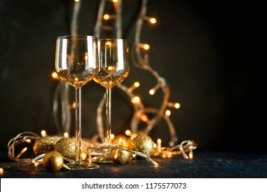 Two glasses for wine and golden Christmas balls against a background of blurred golden lights. Shallow depth of field.