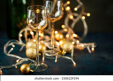 Two glasses for wine and golden Christmas balls against a background of blurred golden lights