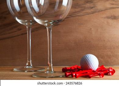 木の背景に、実際の木のベニヤ板から見た、興味深い成長を伴う2つのワインとゴルフ用具