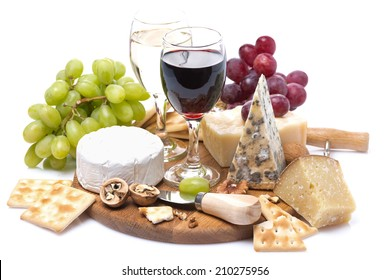 two glasses of wine, grapes, cheese and crackers on a wooden board, isolated on white