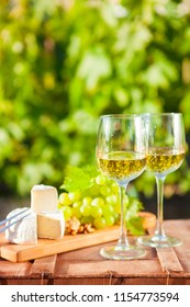Two glasses Wine, grapes, nuts, cheese on vineyard. Dinner, lunch, romantic date, picnic, eating on nature.