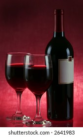 two glasses of wine on red
