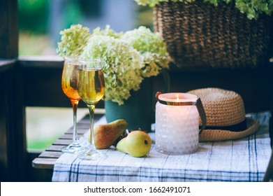 two glasses of wine on summer table decorated with flowers. Wooden country house ot cottage  porch.