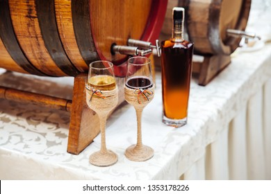 Two glasses with wine ornamented in the Romanian / Moldavian traditional style with the national flag. Various alcohol drinks near wooden barrels.