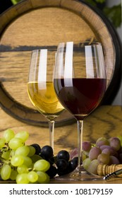 Two glasses of wine, red and white wine with grapes