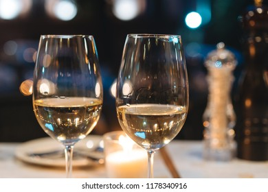 two glasses of wine stand on a festive table