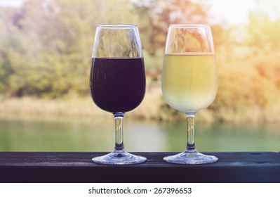 Two glasses of wine, white and red, on wooden rail with country rural scene in background with applied retro style filters and lens flare.