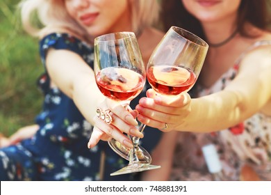 two glasses of wine, wich hold girl friends have a wine celebrate friendship on picknick, girls dayout