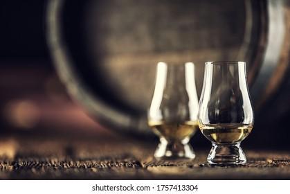 Two Glencairn whisky tasting glasses on vintage wood and dark wooden barrel in the back.