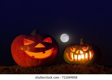 Two glowing pumpkins on the ground and a full moon in the dark blue sky. Picture for decoration on the holiday of Halloween.