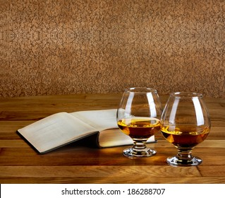 Two goblets of brandy and open book on wooden old counter top