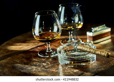 Two goblets of liquor besides smoking cigar sitting in glass ashtray by fancy lighter on a wooden table