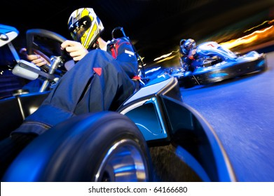 Two go-cart drivers battling in a competitive race on an indoor circuit