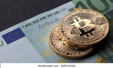 Two gold coins bitcoin stack on paper euro bill