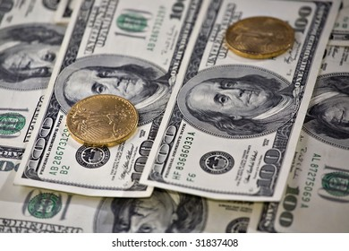 Two gold coins stacked on one hundred dollars bills.  St. Gaudens gold Double Eagle and Franklin one hundred dollar FRN (Federal Reserve Notes) are seen in the image.