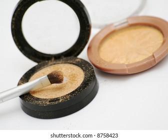 Two gold eyeshadows and brush applicator