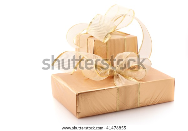 Two gold foil gifts with gold translucent bows isolated on white background.