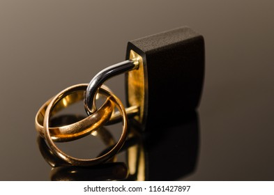 Two gold rings stuck in a black padlock in perpective