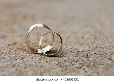 Two gold wedding bands close up on rough sidewalk
