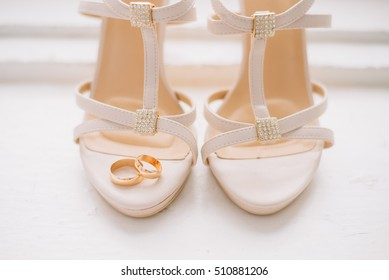 two gold wedding rings lie on a beige bridesmaid shoes