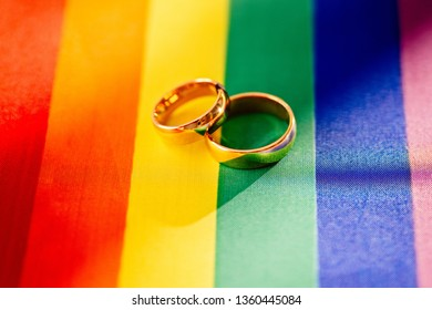 Two gold wedding rings on rainbow lgbt flag. Homosexual marriage. Lgbt rights and law