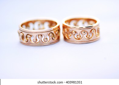 two gold wedding rings on a white background closeup