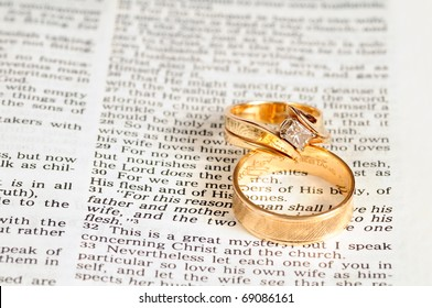 Two gold wedding rings rest on the marriage passage from Ephesians 5 in the Bible