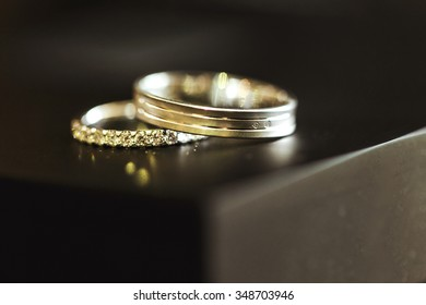 Two golden beautiful encripted wedding rings on table closeup