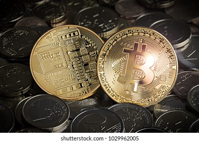 two golden bitcoin on pile stack of euro coins crypto currency financial background concept