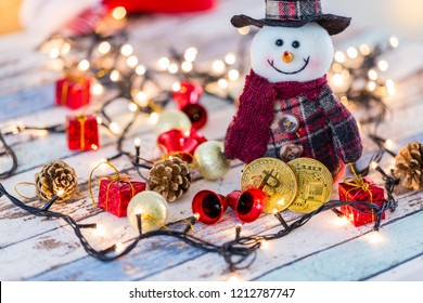 Two golden bitcoins in front of snowman with christmas decors and lights
