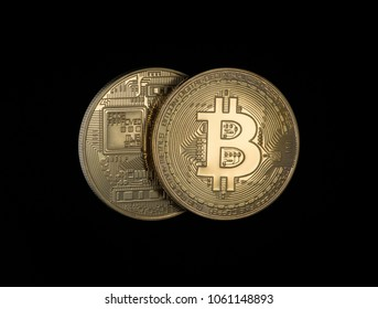 two Golden bitcoins on a black background. electronic money isolated