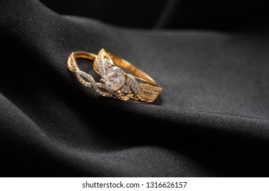 Two golden bracelet , black background ,Corrugated fabric , Diamond