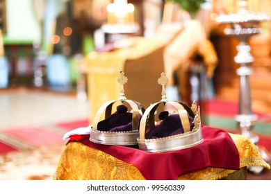 Two golden crown at wedding ceremony in beautiful interior of Saint Trinity Orthodox Convent in Riga, Latvia including candlesticks with many candles. Nice bokeh with copy space in the background.