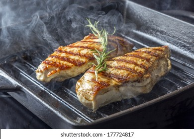 Two golden fried pieces of chicken breast in a griddle pan with rosemary